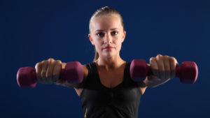 Beautiful young caucasian fitness woman working out with hand weights, arms outstretched building strength.